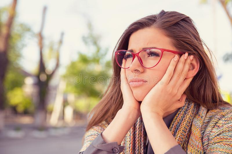 Thoughtful sad young woman looking gloomy sitting outdoors royalty free stock photos