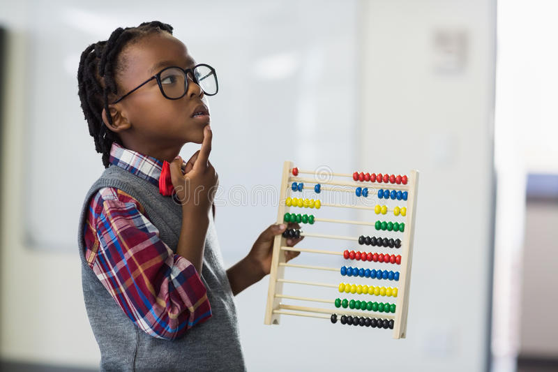 Thoughtful schoolboy using a maths abacus in classroom stock photography