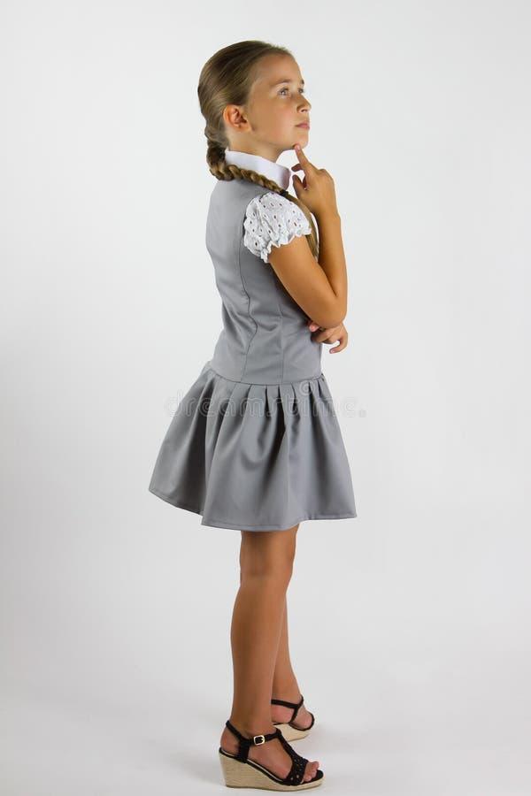 Thoughtful schoolgirl. Cute schoolgirl is worth considering in the studio royalty free stock photo