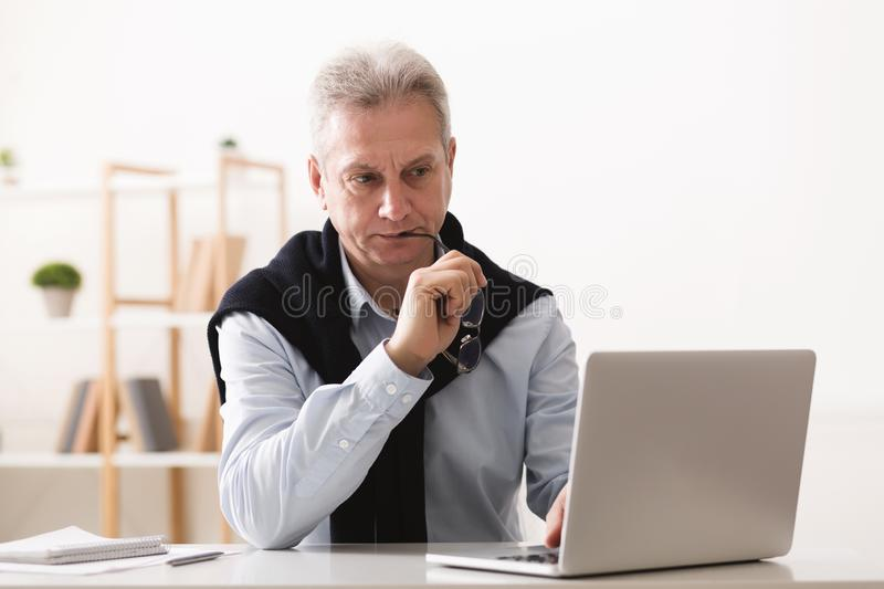 Thoughtful senior businessman looking at laptop at home stock photo