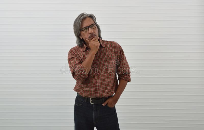 Thoughtful senior businessman in red casual shirt royalty free stock photo