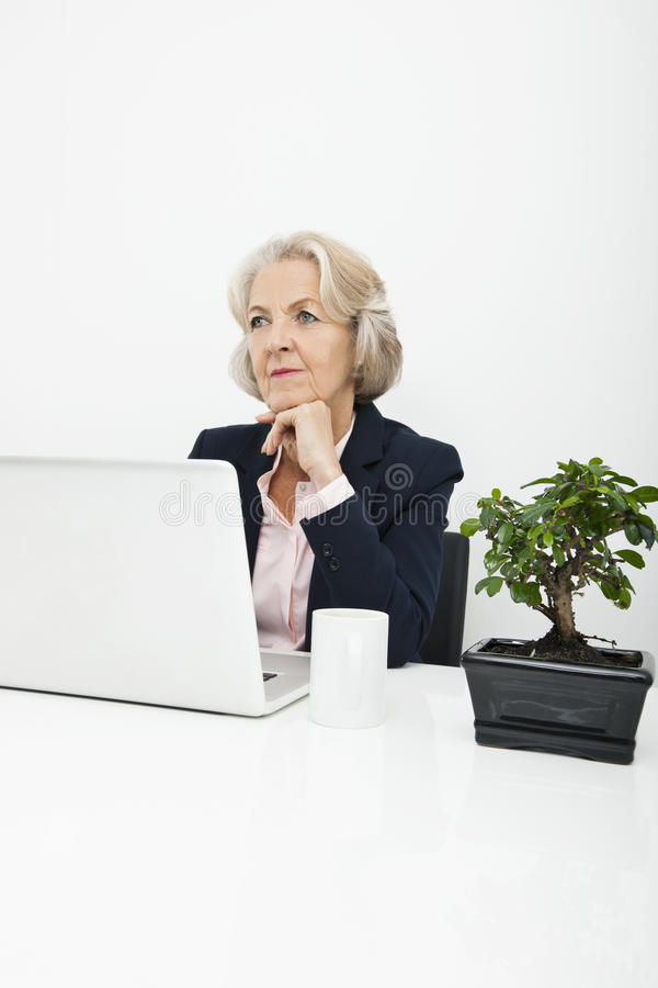Download Thoughtful Senior Businesswoman With Laptop Sitting At Desk In Office Stock Image - Image: 35901439