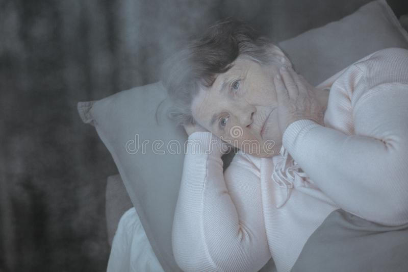 Thoughtful senior woman in bed stock images