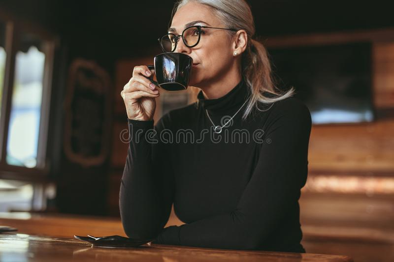 Thoughtful senior woman sitting at cafe drinking coffee stock photos