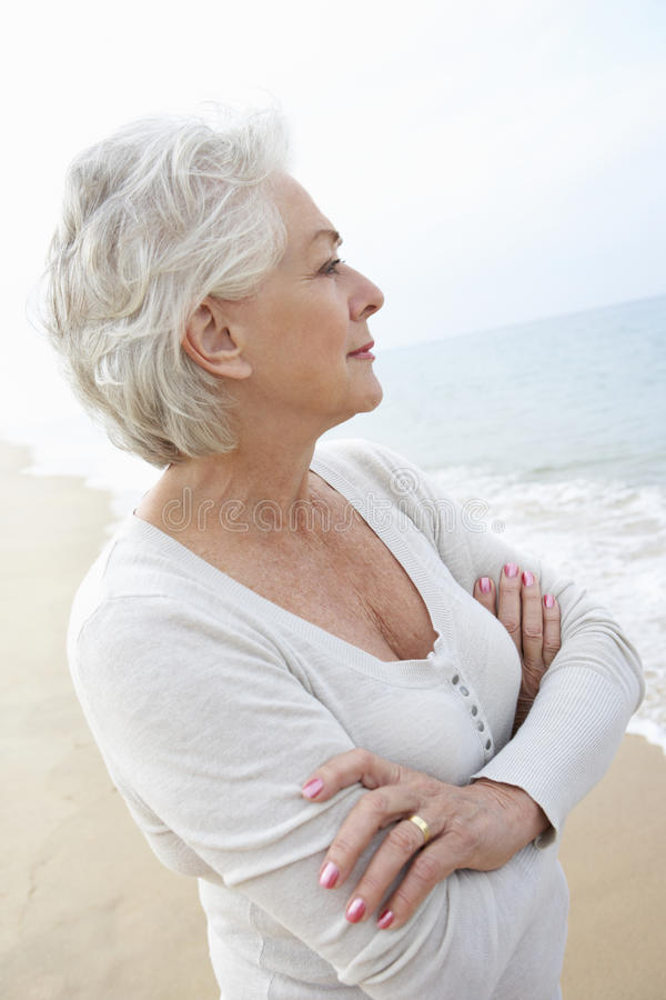 Thoughtful Senior Woman Standing On Beach stock image
