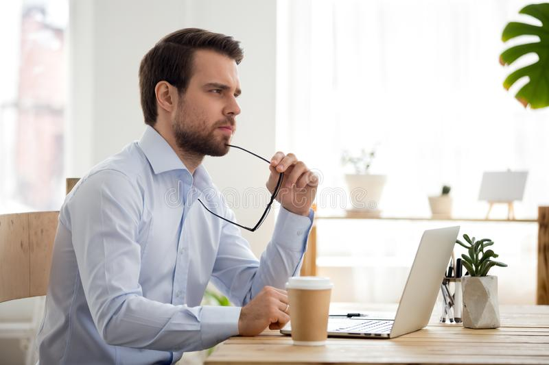 Thoughtful serious businessman lost in thoughts at work with laptop stock photo