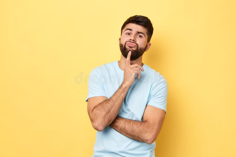 Thoughtful serious Caucasian young man touches chin with finger stock image