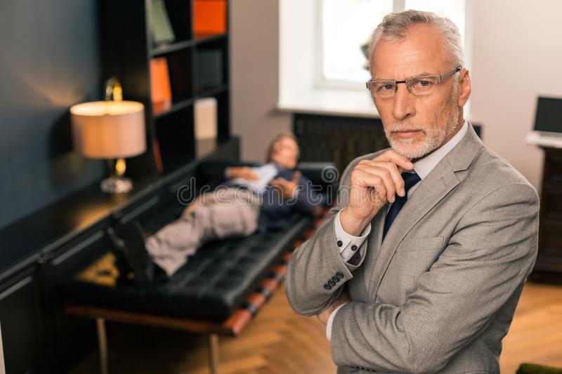 Thoughtful serious doctor standing next to his patient stock photography