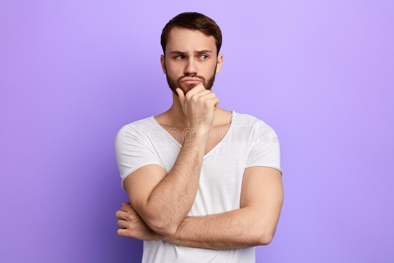 Thoughtful serious man with hand on the chin looking aside stock photo