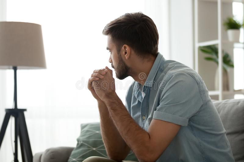 Thoughtful serious man sitting on sofa at home, lost in thoughts stock image