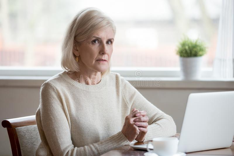 Thoughtful serious mature woman thinking of problem solution nea royalty free stock photography