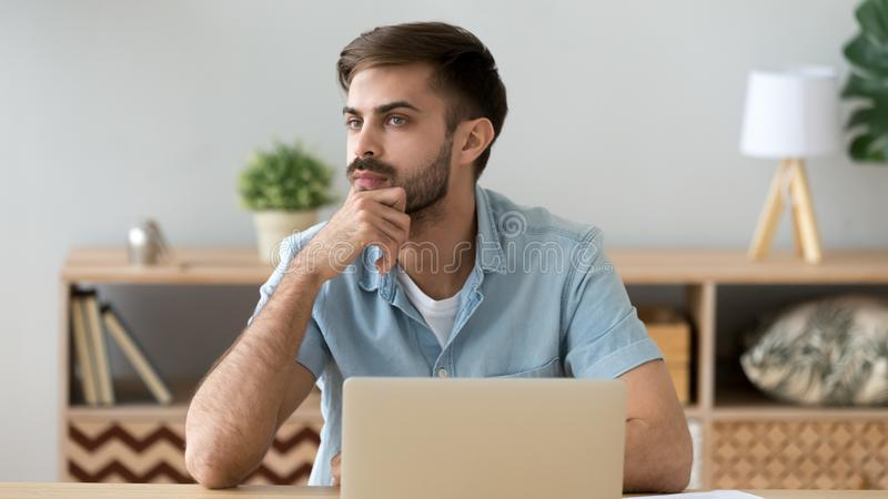 Thoughtful serious student or office worker thinking about online project stock photos