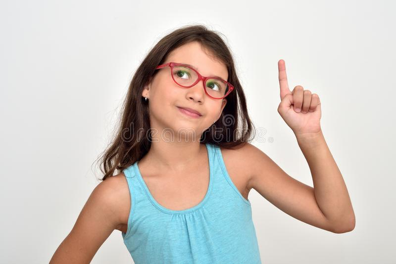 Thoughtful young girl with index finger up royalty free stock image