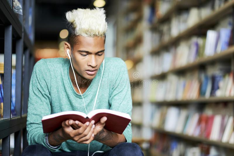 Thoughtful student in earphones reading book stock photography