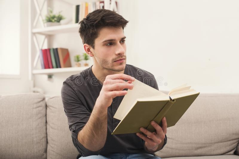 Cozy home. Young thoughtful man with book stock photography