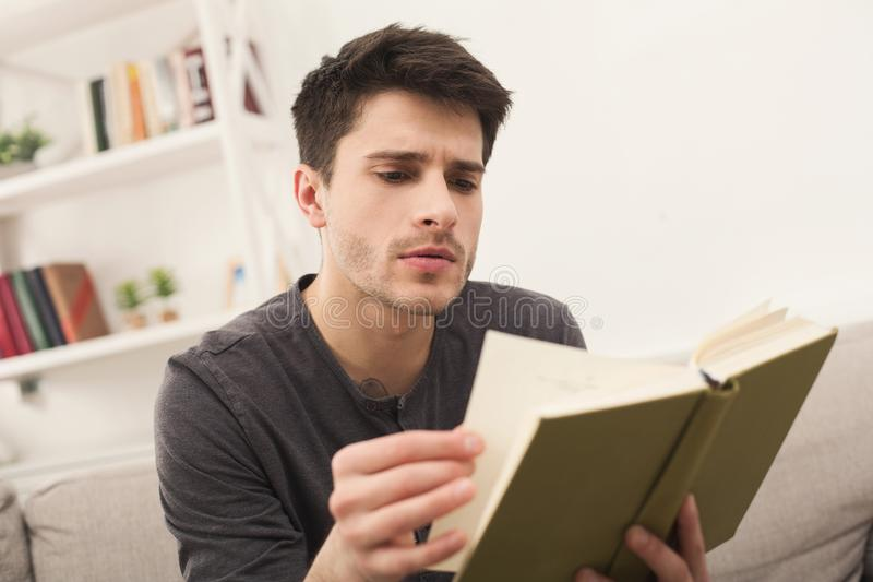Cozy home. Young thoughtful man with book royalty free stock photos