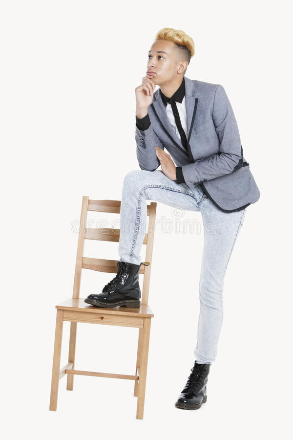 Thoughtful Teenage Boy Standing With One Leg On Chair Over Gray ...