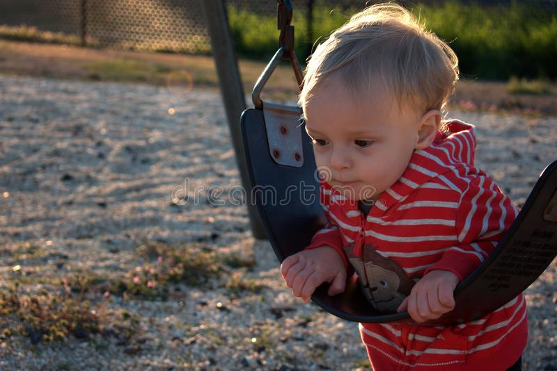 Thoughtful Toddler. Cute toddler boy contemplates the wonders of the universe while playing on a swing royalty free stock photo