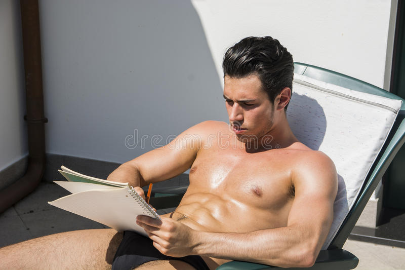 Thoughtful topless young man in deckchair with pencil and notebook. Topless handsome man in panties on deckchair looking pensively away with pencil and notebook royalty free stock photo