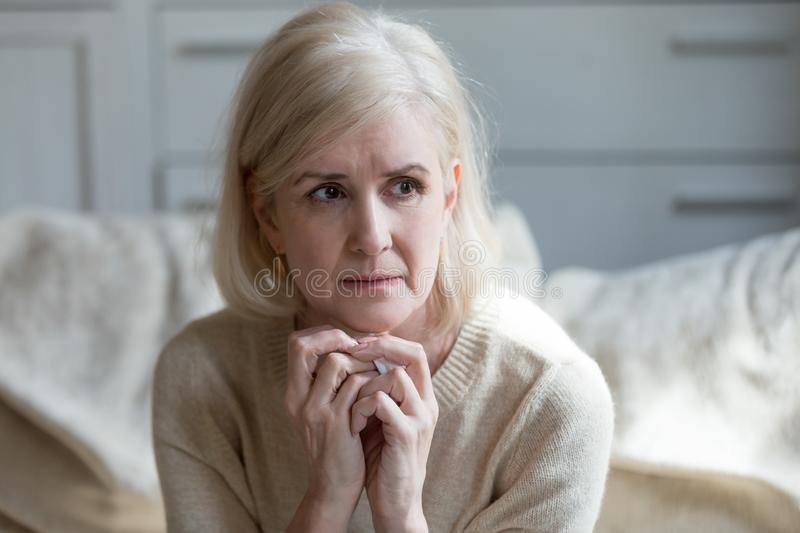 Thoughtful upset mature lady crying thinking of loneliness or gr royalty free stock images