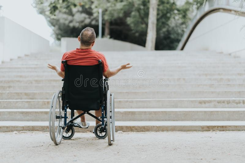 Thoughtful wheelchair man, can not climb the stairs has mobility problems stock photo