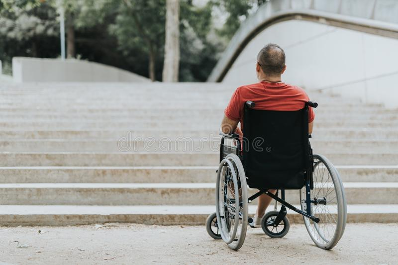 Thoughtful wheelchair man, can not climb the stairs has mobility problems royalty free stock image