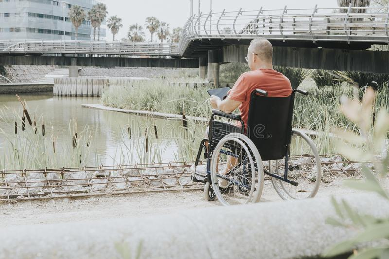 Thoughtful man in a wheelchair. Thoughtful wheelchair man looking at a lake in the city, assist, assisting, detailed, helping, operation, surgery, rehab royalty free stock photo