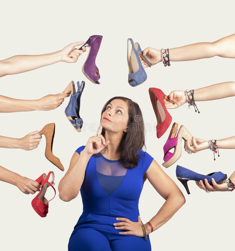 Thoughtful woman deciding what shoe she wants. She`s surrounded by shoes royalty free stock photo
