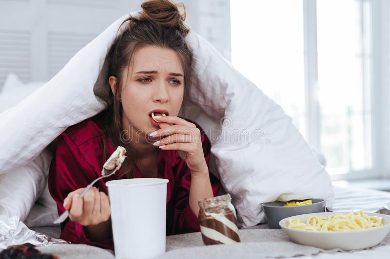 Thoughtful woman eating chips thinking about future. Eating chips. Thoughtful stressed woman with messy hair eating chips while thinking about future lying in royalty free stock photos