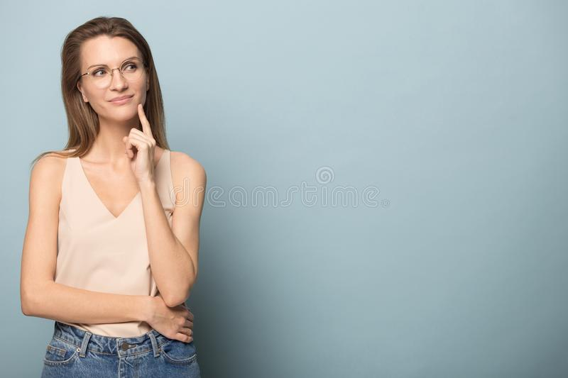 Thoughtful woman touch chin, looking to right at copy space stock images