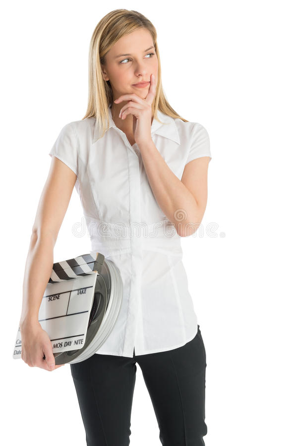 Thoughtful Woman Holding Film Slate And Reel While Looking Away. Thoughtful young woman with hand on chin holding film slate and reel while looking away against royalty free stock photography