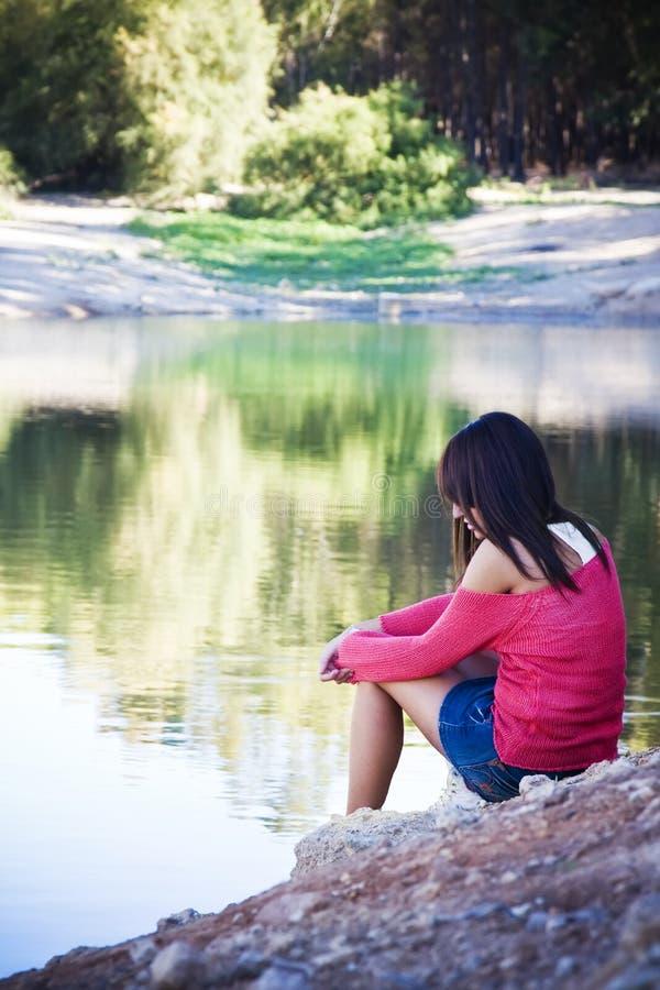 Thoughtful woman in lake shore stock image