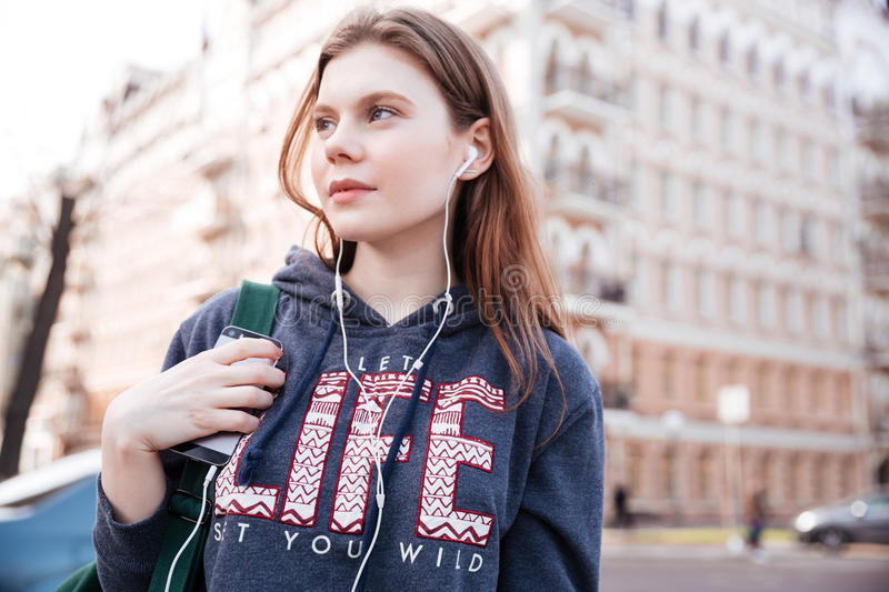 Thoughtful woman listening to music from mobile phone on street stock photography