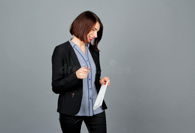 Thoughtful woman looking away while smile. Write on notes. royalty free stock images