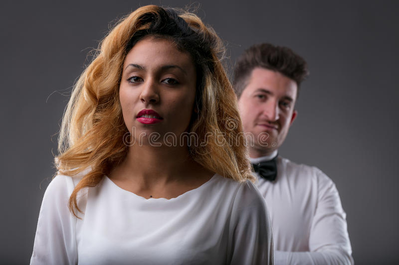 Thoughtful woman looking to you with a man controlling her royalty free stock photos