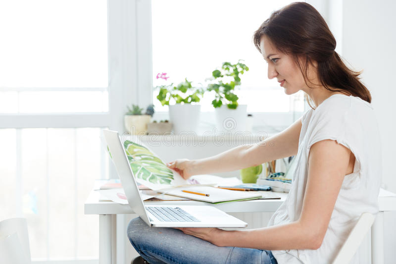 Thoughtful woman painter using laptop in art studio stock image