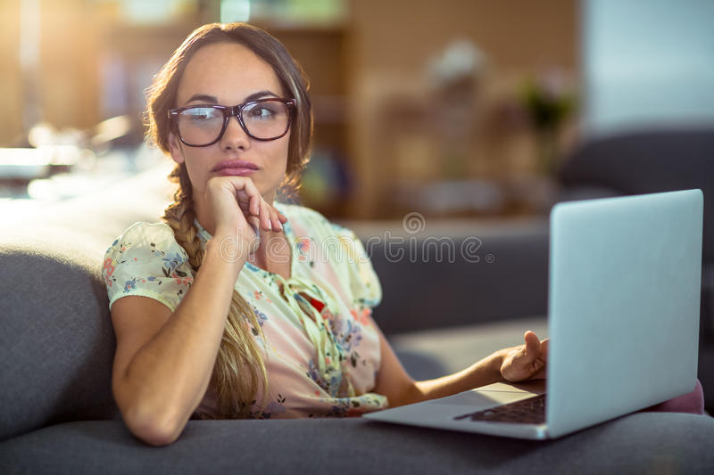 Thoughtful woman sitting on sofa and using laptop royalty free stock photo