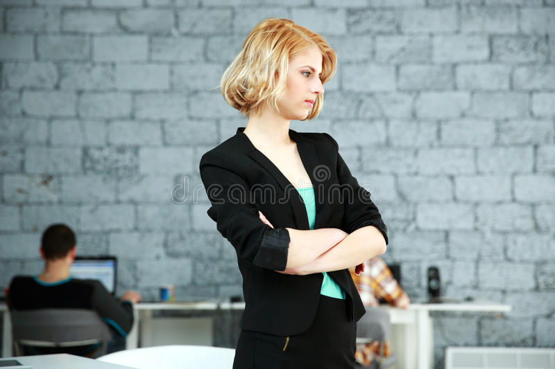 Thoughtful woman standing with arms folded. Young thoughtful woman standing with arms folded in office stock photos