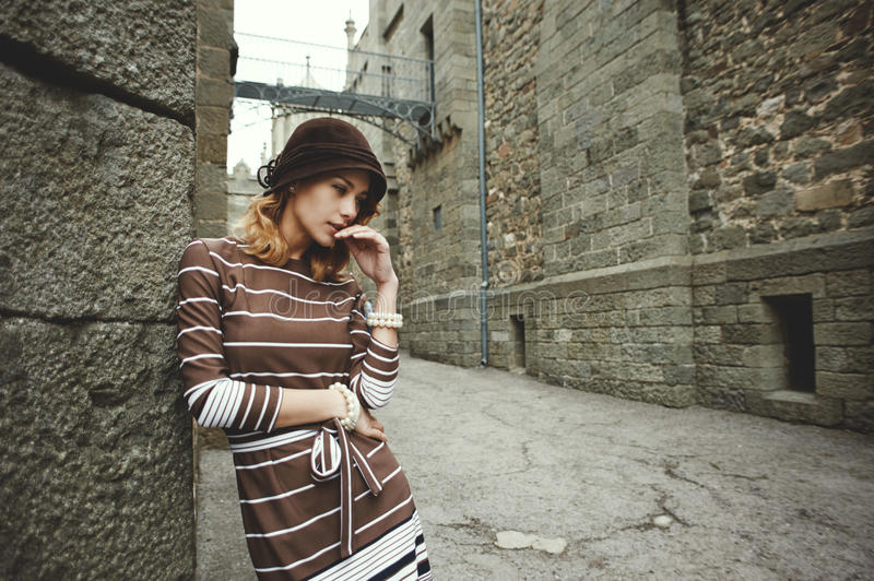Thoughtful woman standing leaning against wall of ancient castle stock photos