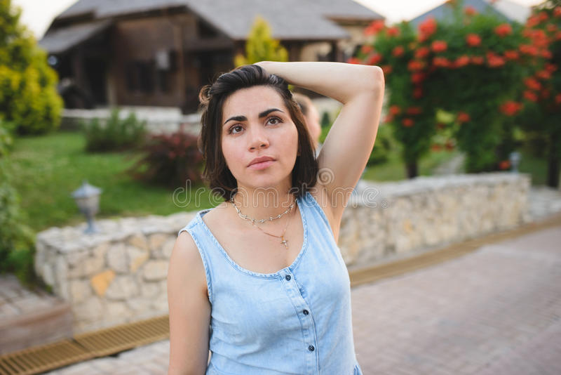 Thoughtful Woman. Touching hair in yard royalty free stock images