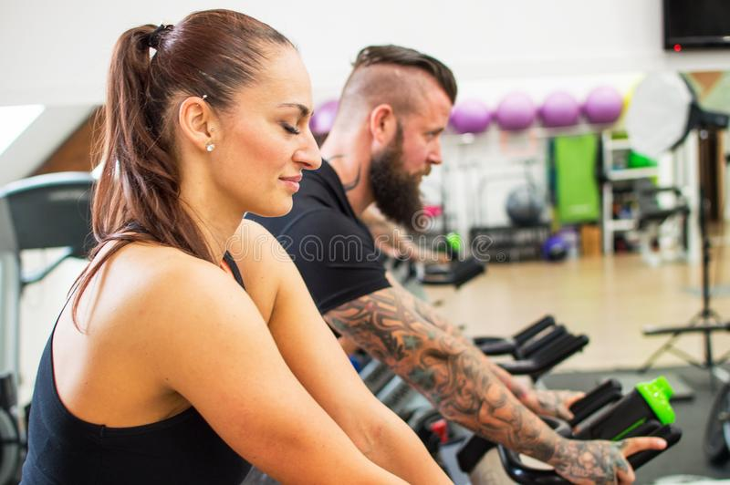 Thoughtful woman in a gym beside a tattooed man. stock images