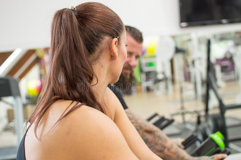Thoughtful woman in a gym beside a tattooed man. stock image