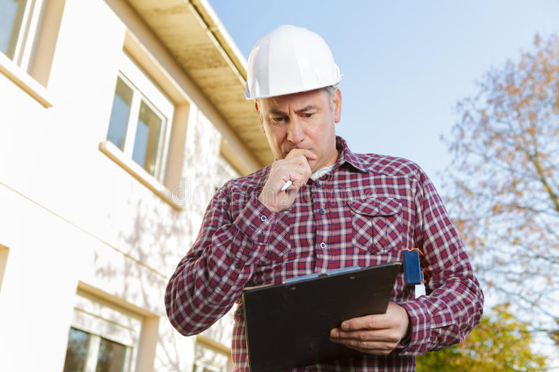 Thoughtful worker builder in hardhat on background construction royalty free stock photos