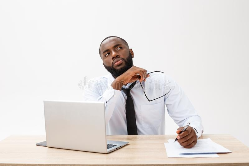 Thoughtful young african american businessman working on laptop computer royalty free stock photography