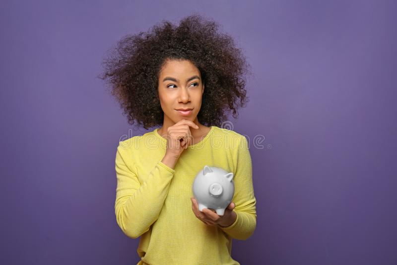 Thoughtful young African-American woman with piggy bank on color background. Savings concept stock image