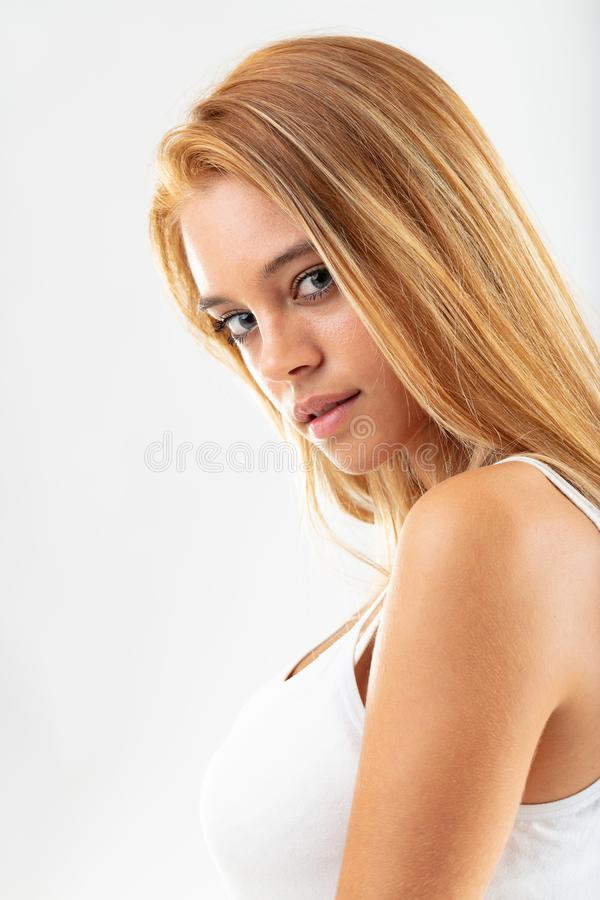 Thoughtful young attractive teenage girl. Thoughtful young attractive blond teenage girl looking back, over her shoulder at the camera with a speculative stock images