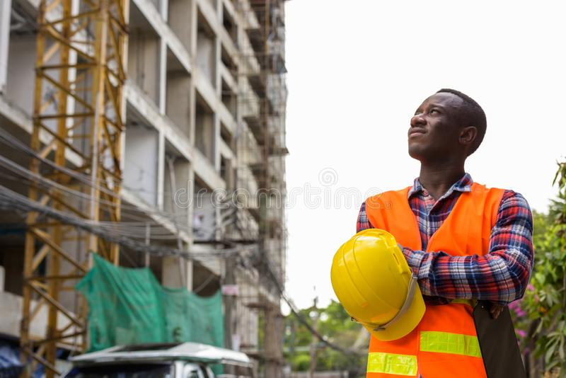 Thoughtful young black African man construction worker holding c stock photo