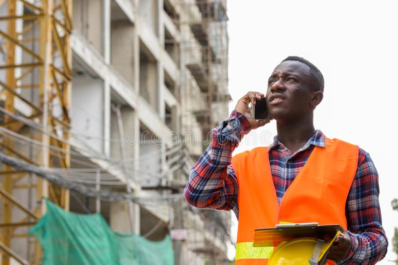 Thoughtful young black African man construction worker talking o stock photo