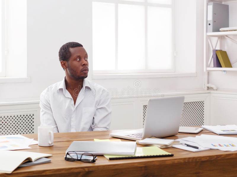 Thoughtful young black man enjoying his successful business royalty free stock image
