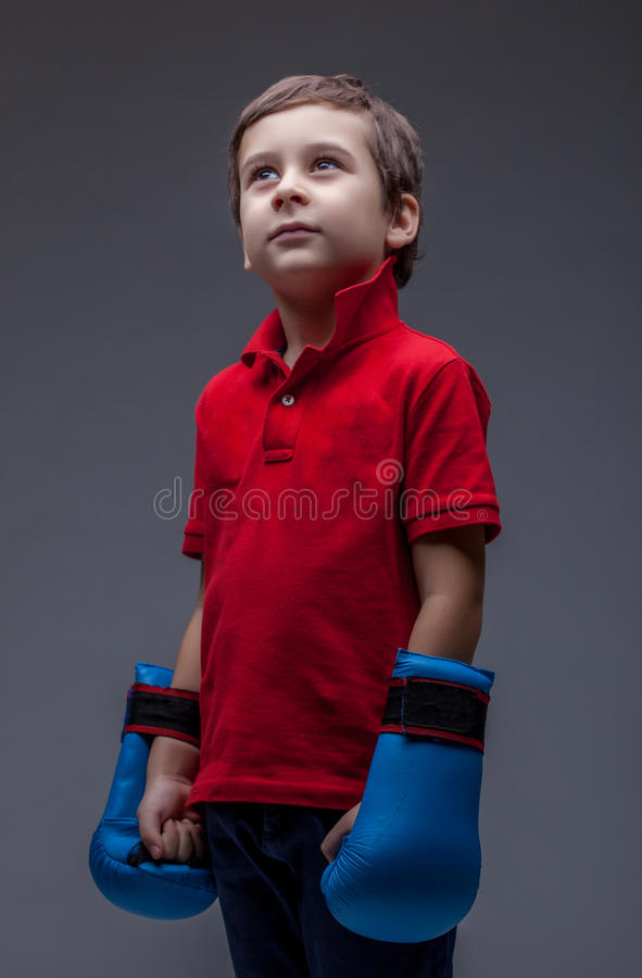Thoughtful young boy posing in boxing gloves royalty free stock images
